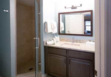 Bathroom with sink, large mirror, and walk-in shower in a villa in North Village at Orange Lake Resort near Orlando, Florida