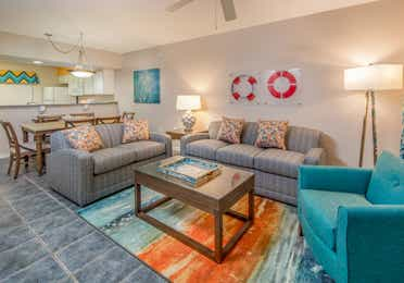 Living room with two couches, an accent chair, and coastal decor in a two-bedroom villa at Panama City Beach Resort