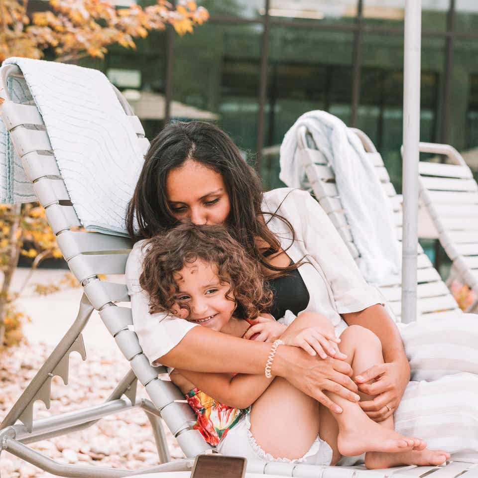 Mother snuggling child outside of pool at Williamsburg Resort.