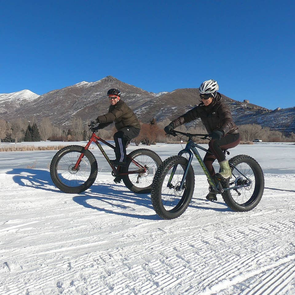 Featured Contributor, Jessica Averett (right), wears a winter jacket, sunglasses, and white bike helmet while riding a Fat Tire bike in the snow next to a man in front of the mountains.