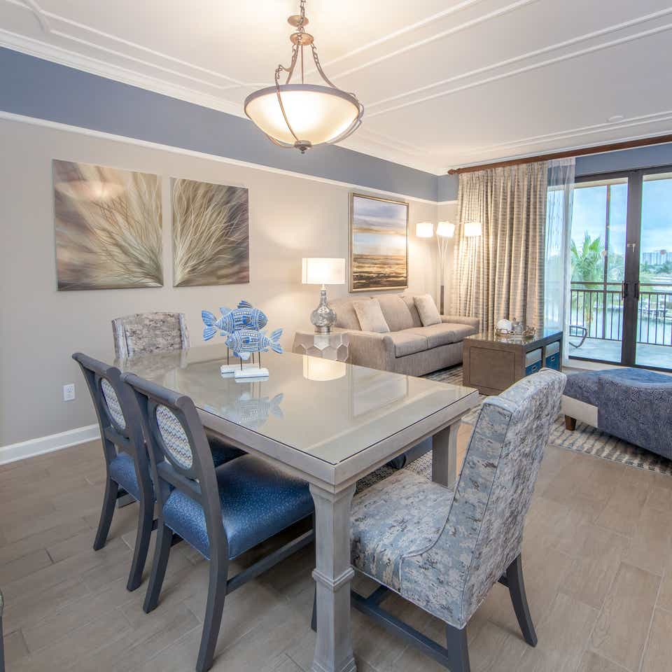 Dining room table with six chairs and coastal decor in a three-bedroom villa at Sunset Cove Resort in Marco Island, Florida