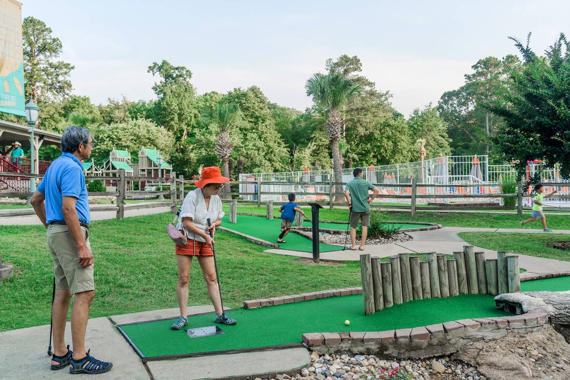 An older Asian man (left) and woman (right) play mini golf near two young Asian boys (right) at our Villages resort in Flint, Texas.