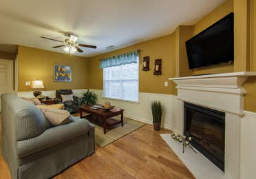 Living room with fireplace and TV in a three-bedroom ambassador villa at the Holiday Hills Resort in Branson Missouri.