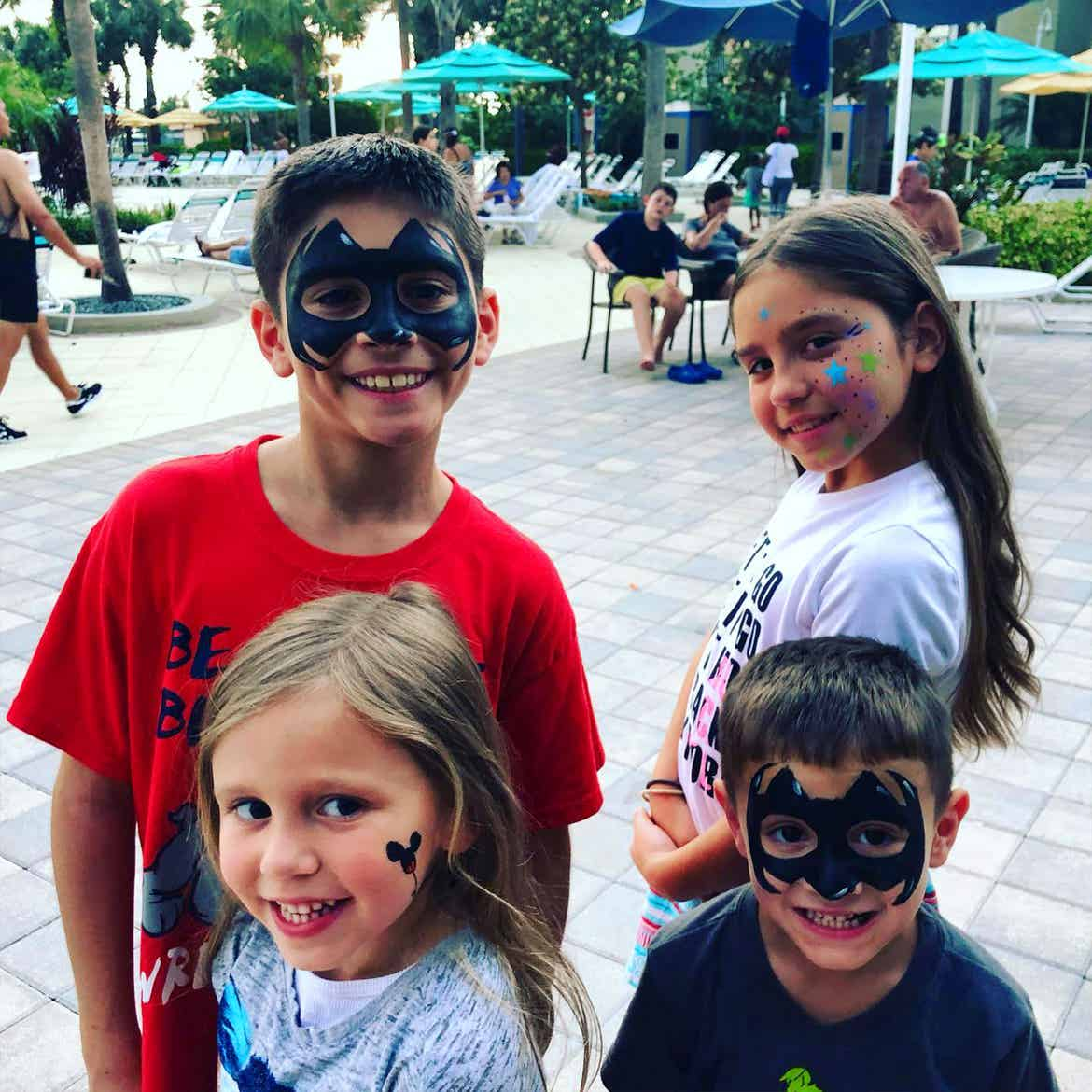 Featured Member, Sara Perezes family stands outside of our River Island pool wearing various face paintings.