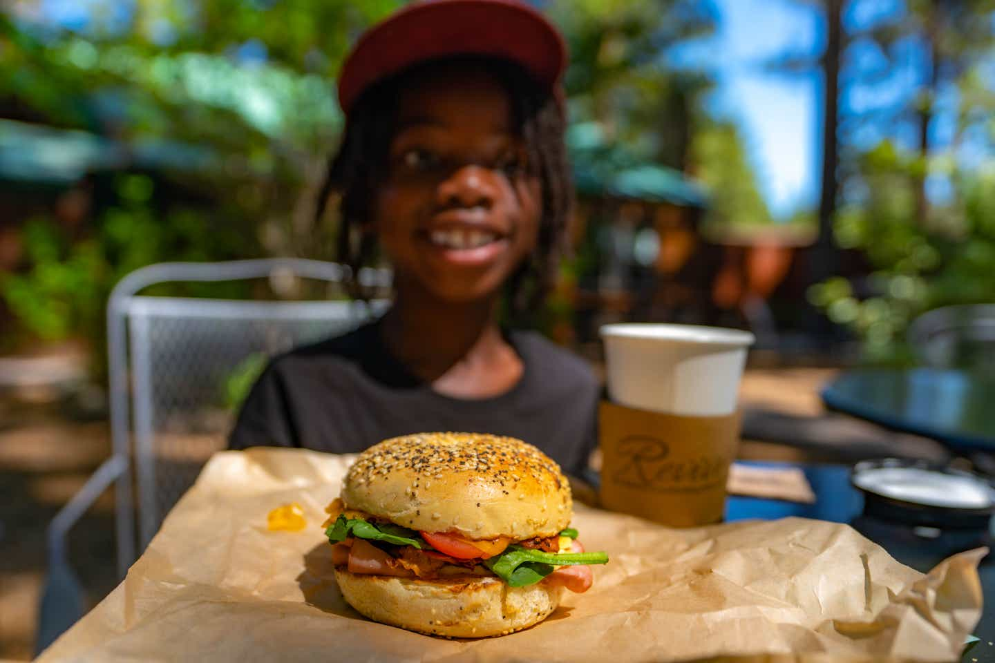 A breakfast sandwich and coffee and Karen's son smiling in the background.