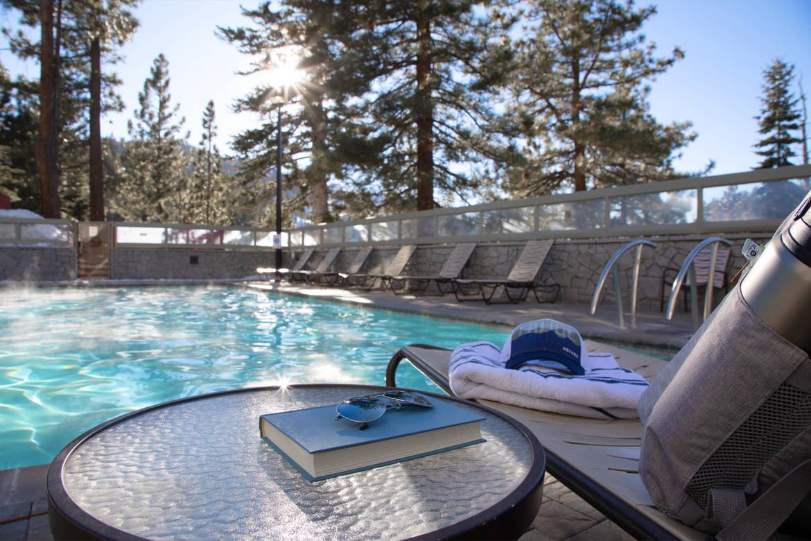 A hat and aviator sunglasses placed on a table near an outdoor pool at Tahoe Ridge Resort in Stateline, NV