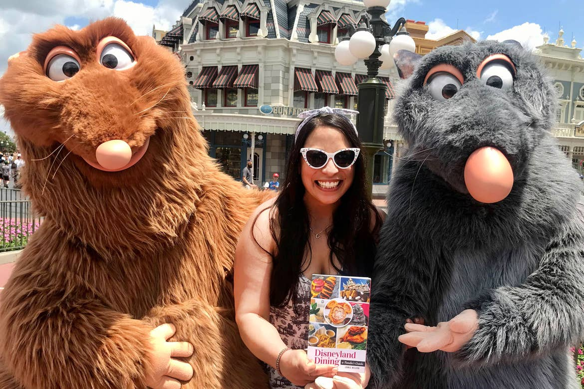 Jamie Nelson (middle) holds her authored book and stands next to Emile (left) and Remy (right) at Walt Disney World Resort.