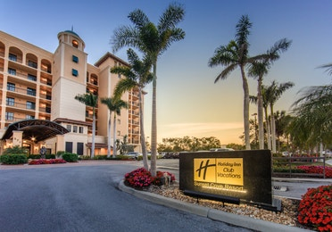 Property sign and building surrounded by palm trees at Sunset Cove Resort