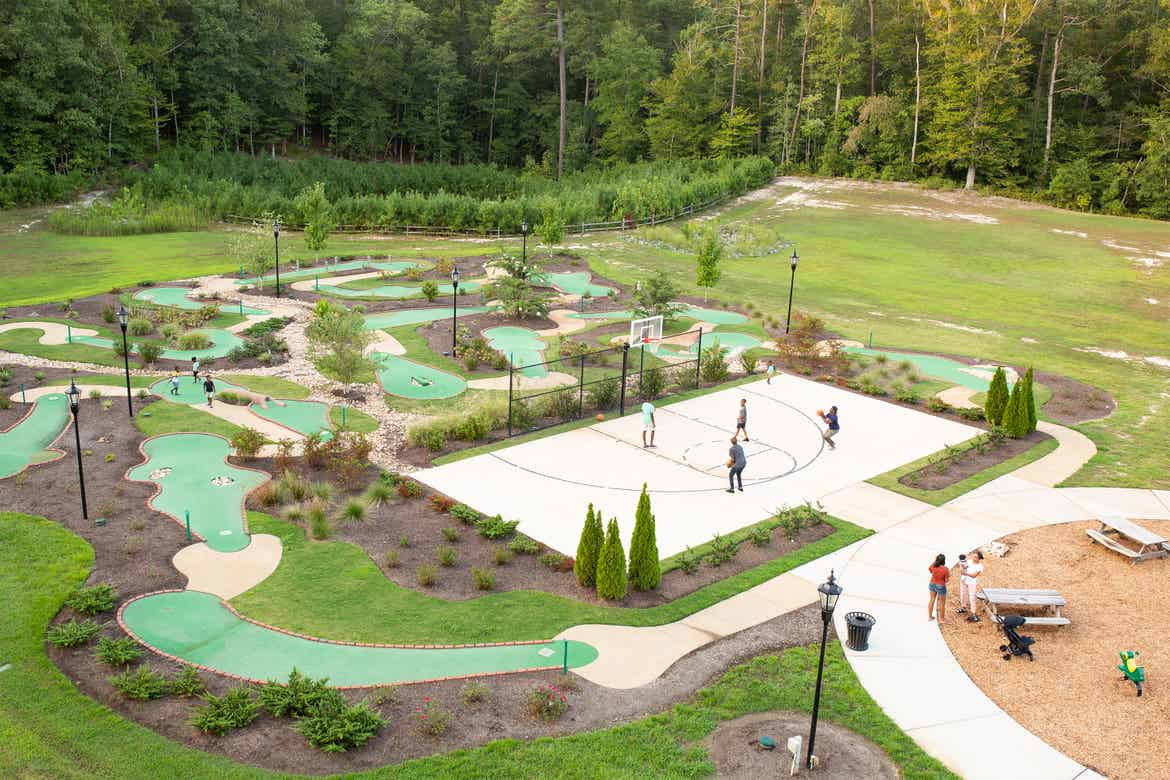 Families enjoying outdoor amenities such as mini-golf and basketball surrounded by lush landscapes at our Williamsburg resort in Williamsburg, Virginia.