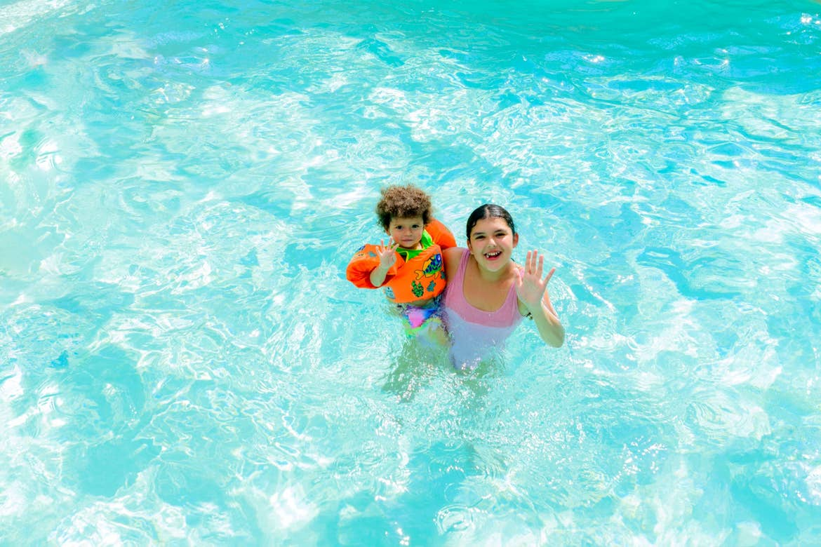 A toddler boy (left) and tween girl (right) float in a pool.