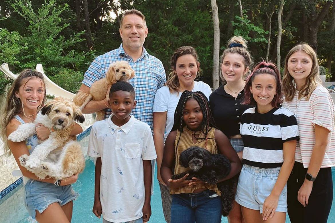 Mindy and her family pose in front of their pool with some of their pets.