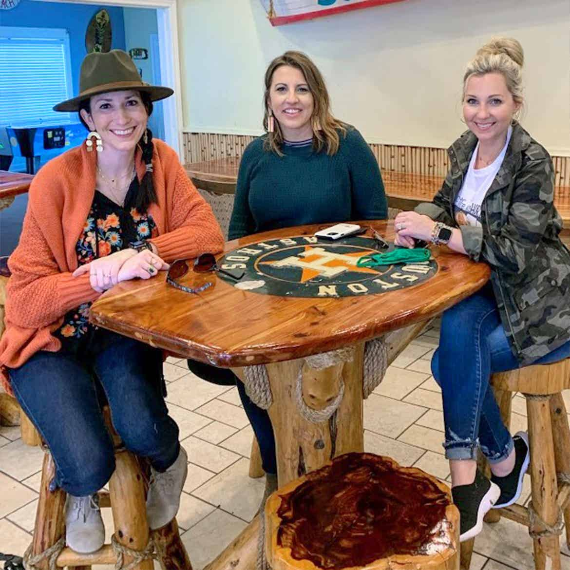 Featured Contributor, Amanda Nall (right) poses with her two friends at a table in Galveston, Tx.