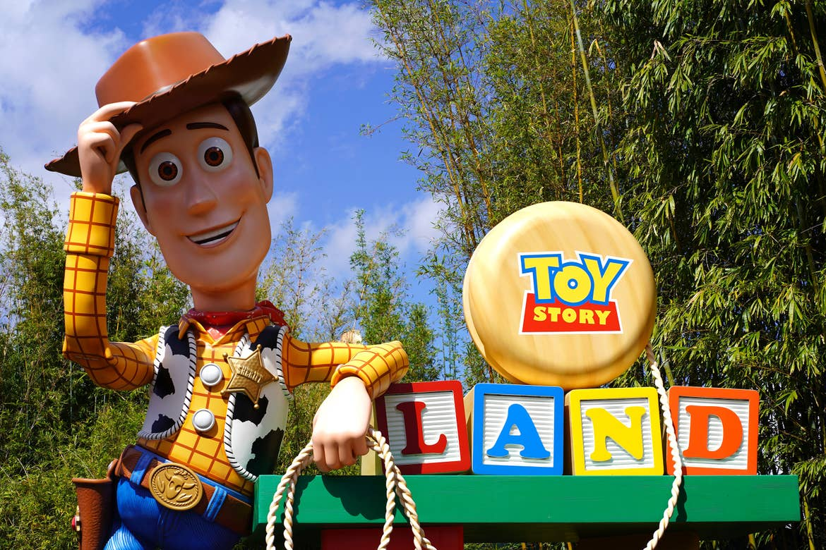 A large Sheriff Woody tilts his hat while holding a lasso and resting his arm on the 'Toy Story Land' marquee in Disney's Hollywood Studios at Walt Disney World Resort.
