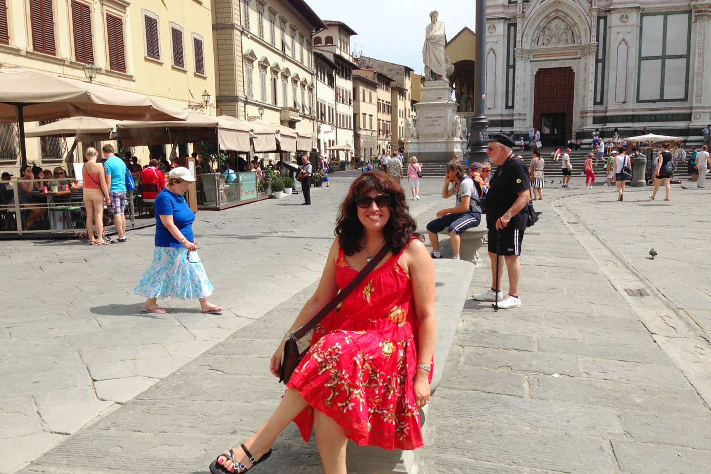 Author, Jennifer Probst, sits on a bench in the middle of Venice wearing a red sundress and sunglasses with a black bag slung across her shoulder.