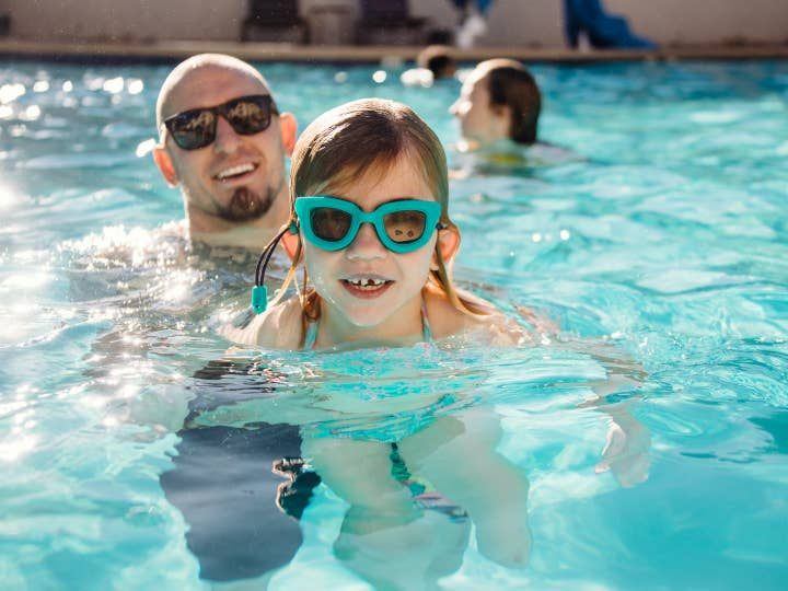 Father and daughter swimming in outdoor pool at Desert Club Resort in Las Vegas, Nevada.