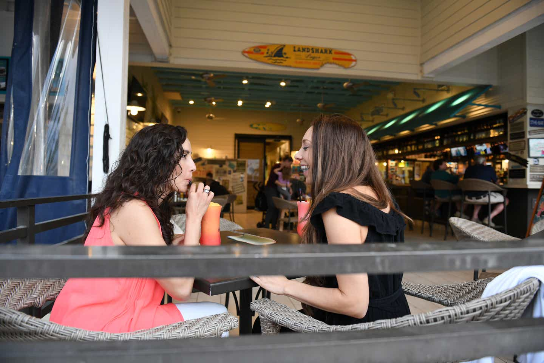 Raff and her wife enjoying fruity cocktail drinks at Breezes Restaurant & Bar at Orange Lake Resort