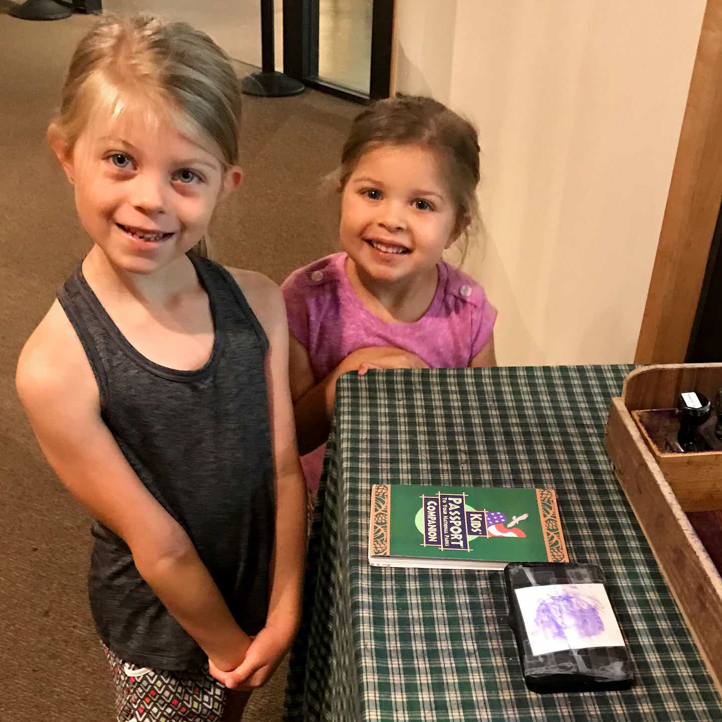 Author, Chris Johnstons' daughters, Kyndall (left), and Kyler (right) pose with their Passport stamp booklet.