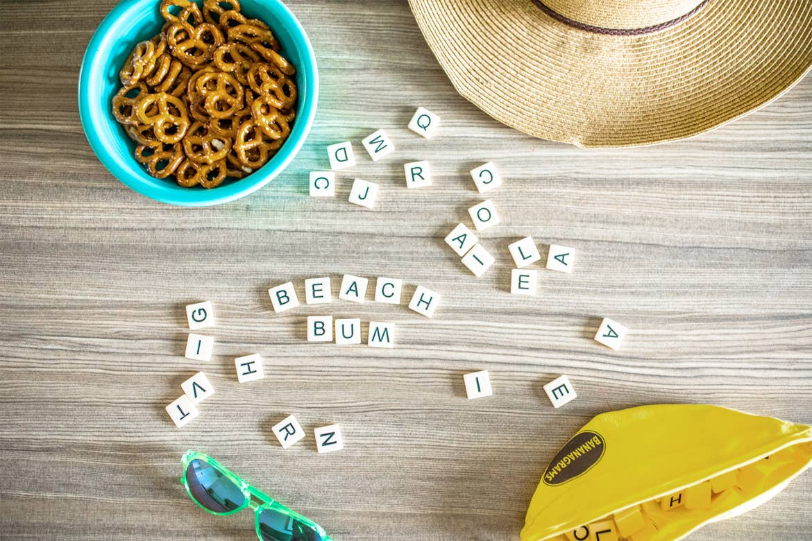 A game of Bananagram tiles placed that read 'Beach Bum' surrounded by hats, sunglasses and snacks.