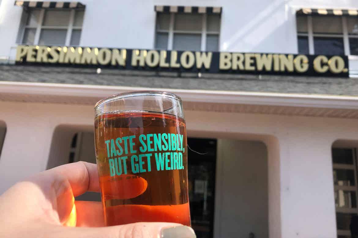 Exterior marquee that reads, 'Persimmon Hollow Brewing Co. and a hand holding a beer glass that reads, 'Taste sensibly, but get weird.'