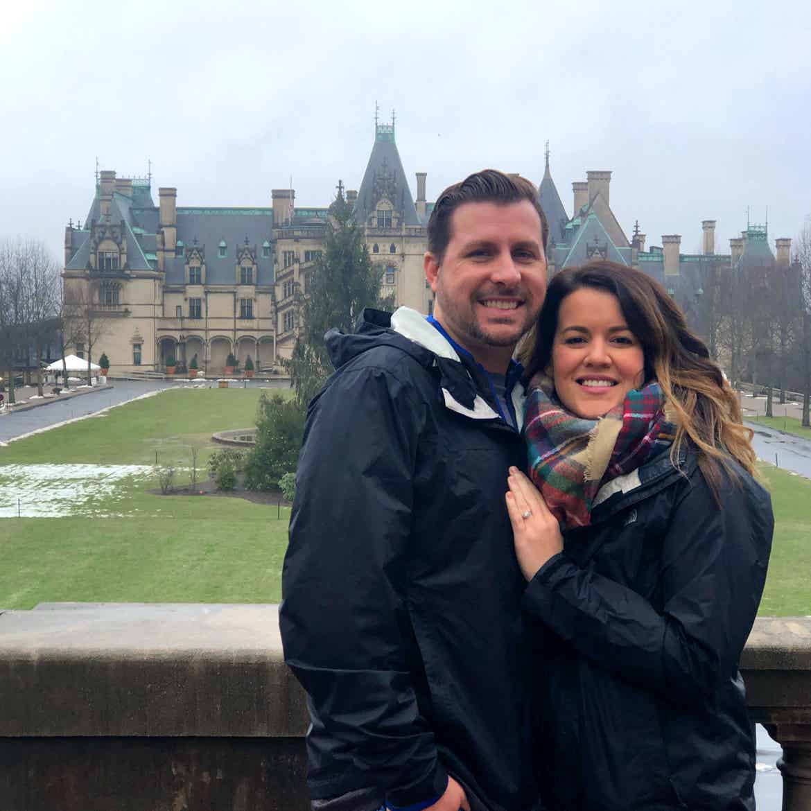 Author, Jenn C. Harmon (right), and husband (left) stand in front of the Biltmore Estate wearing black jackets and a scarf on a grey cloudy day.