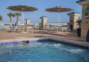 Outdoor pool near tables and chairs at Panama City Beach Resort