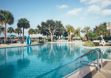 Pool with sun chairs surrounded by palm trees in the West Village at Orange Lake Resort near Orlando, Florida
