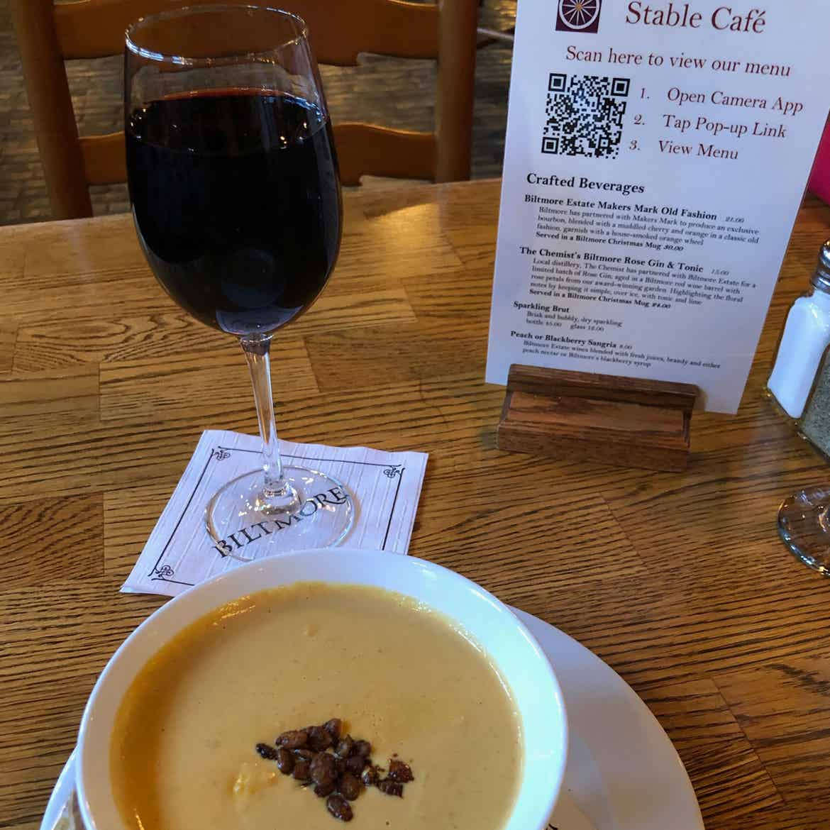 A glass of red wine and the pumpkin bisque are placed on a table near the QR menu at the Stable Cafe.