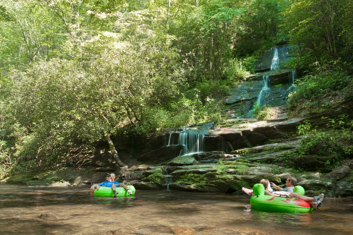 A family tubing down a river past a waterfall.