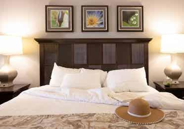 Closeup of sun hat sitting on bed in a villa in East Village at Orange Lake Resort near Orlando, Florida