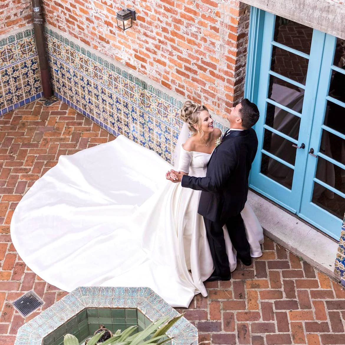 A Latinx groom wearing a black suit and (right) and a caucasian bride with a long train (left) dance with each other in front of a brick facade.