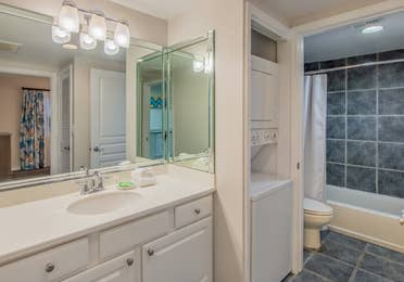 Bathroom with shower/tub combination, toilet, washer/dryer, and sink with large mirror in a two-bedroom villa at Panama City Beach Resort