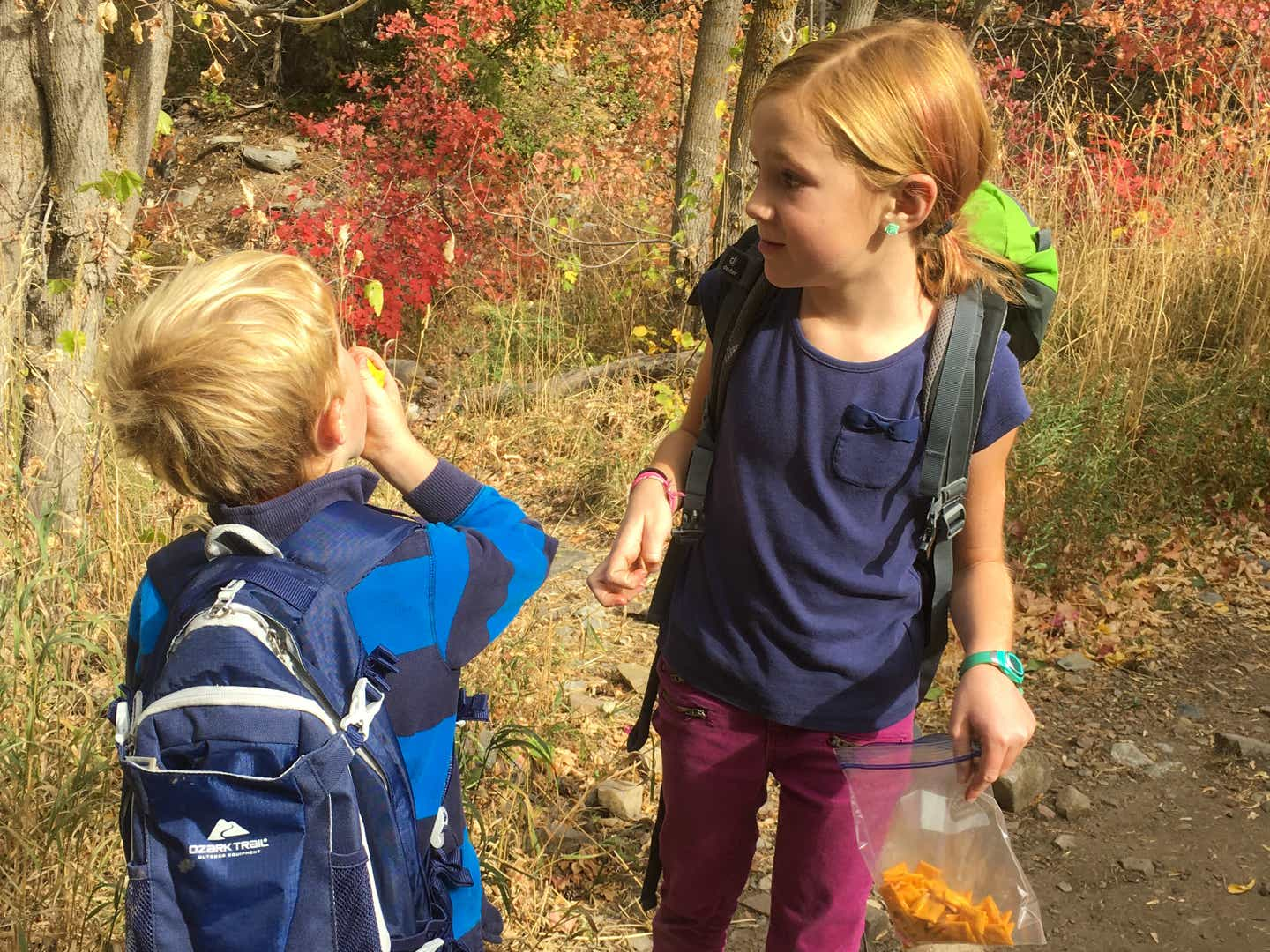 Jessica's daughter and son stopping for a break to eat snacks on their hike