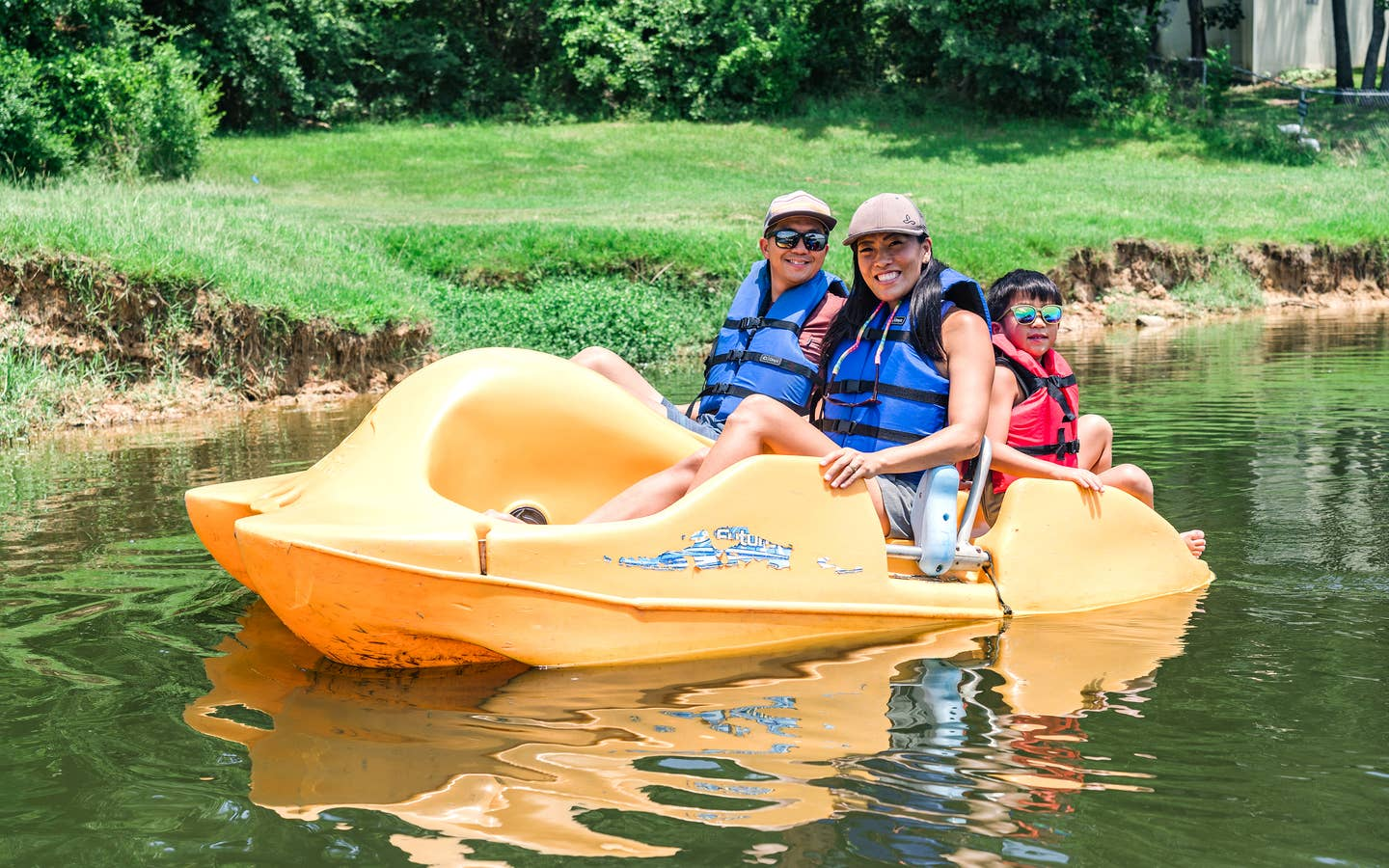 An Asian Male (left), female (middle) and young child (right) wear blue life vests, sunglasses and various hats while riding on a yellow paddleboat in a lake.