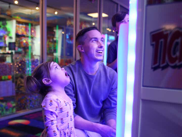 A young man and toddler girl playing video games in a game room