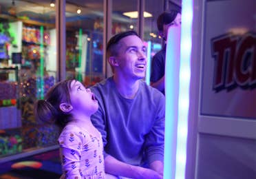 A young man and toddler girl playing video games in a game room.