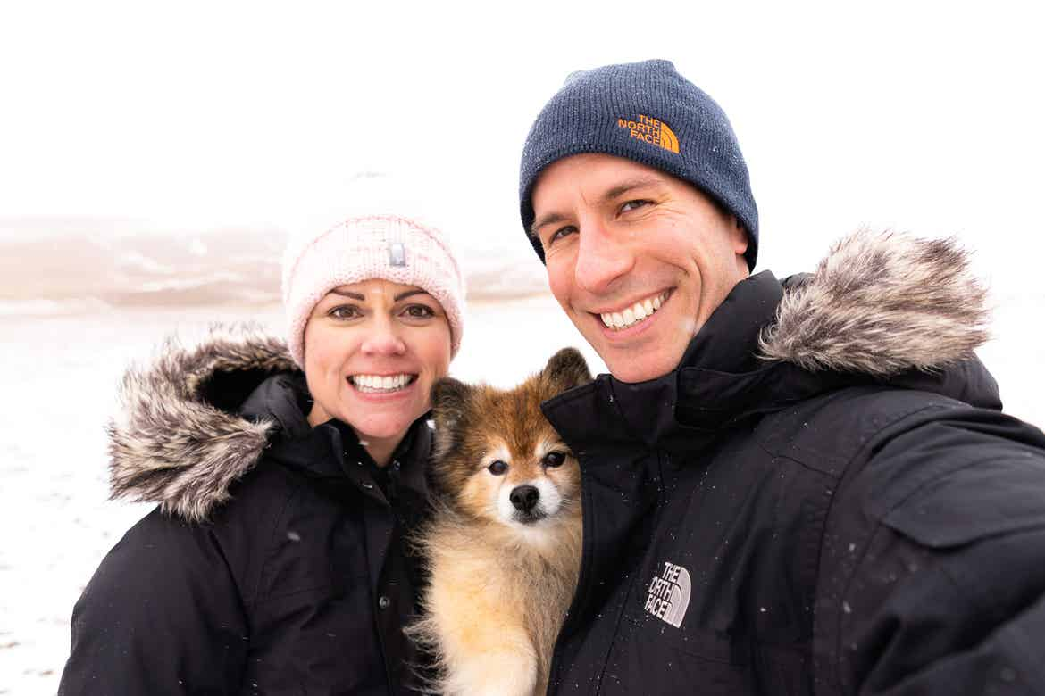 Authors, Lauren Layne and Anthony LeDonne, stand in winter apparel with Bailey the Pomeranian at the Great Sand Dunes National Park and Preserve.