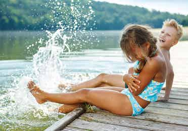 Two toddlers splashing water in the lake on a pier