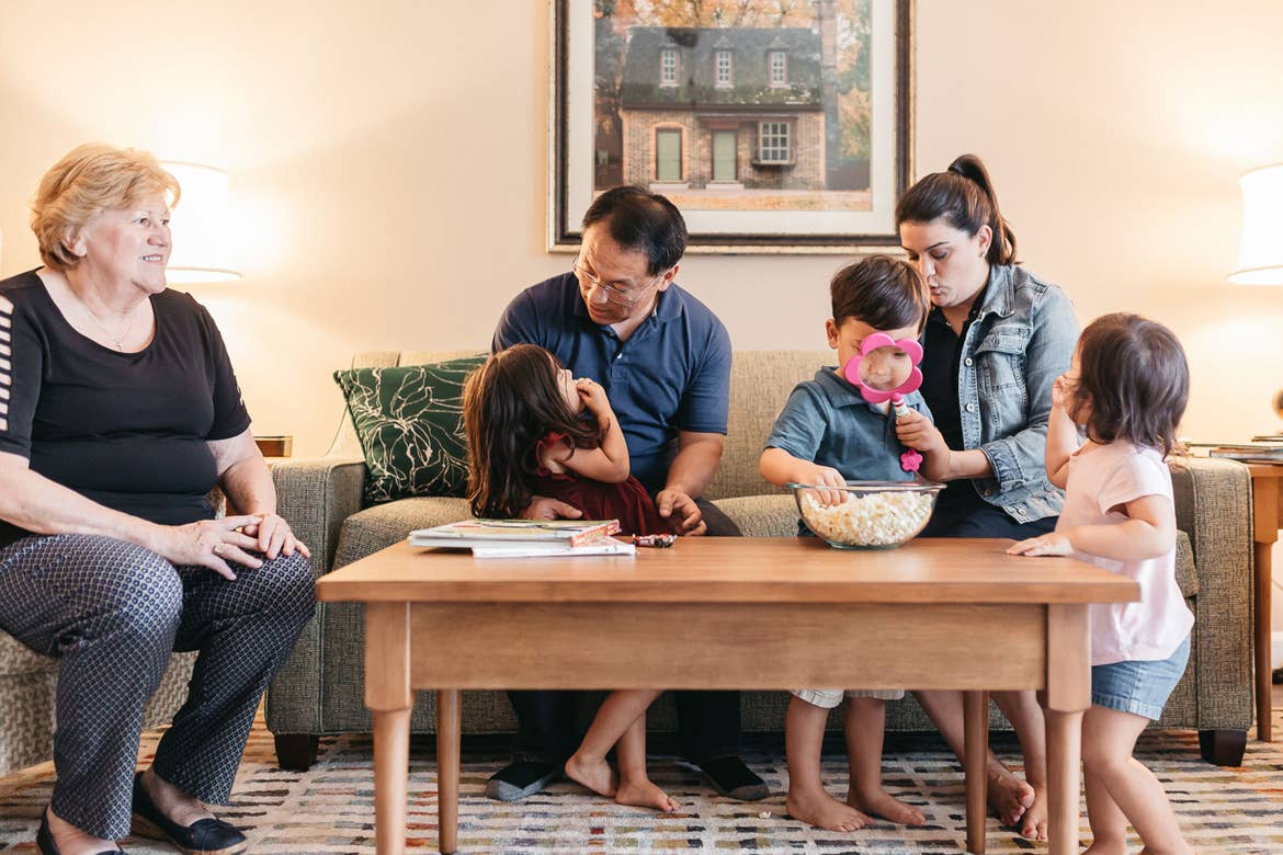 (Left to right) Angelica's mom, Angelica's husband, featured Contributor, Angelica Kajiwara, and her three children sit in the living room of a villa of our Williamsburg resort in Williamsburg, Virginia.