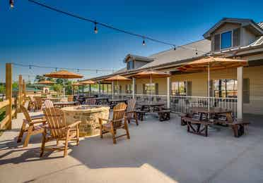 Outdoor tables with chairs and fire pits at Piney Shores Resort in Conroe, Texas