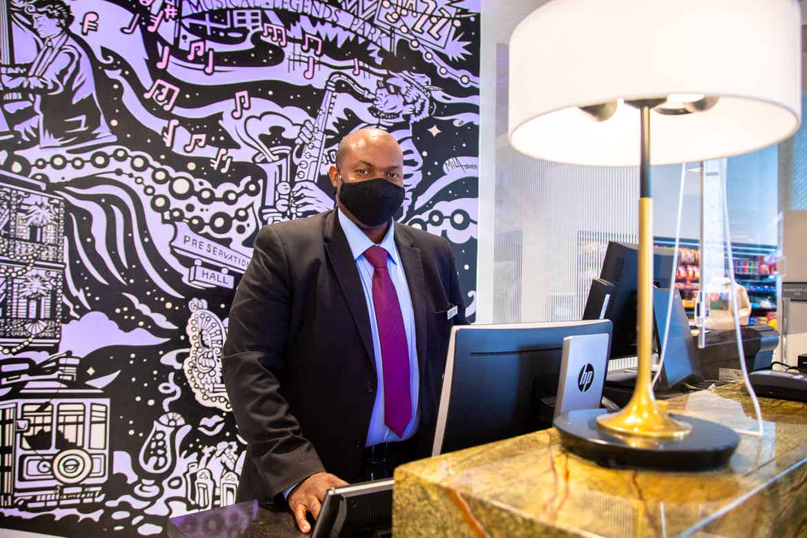 HICV Team Member stands in front of a mural with animated projection mapping in various colors of purple, orange, yellow and magenta featured in the lobby of our resort in New Orleans, Louisiana.