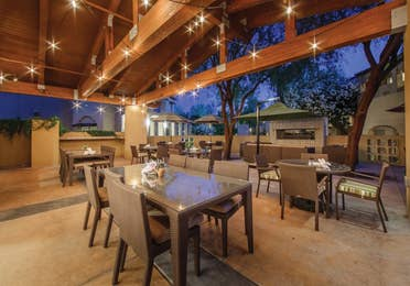 Outdoor dining area under a large patio with market lighting at Scottsdale Resort in Arizona