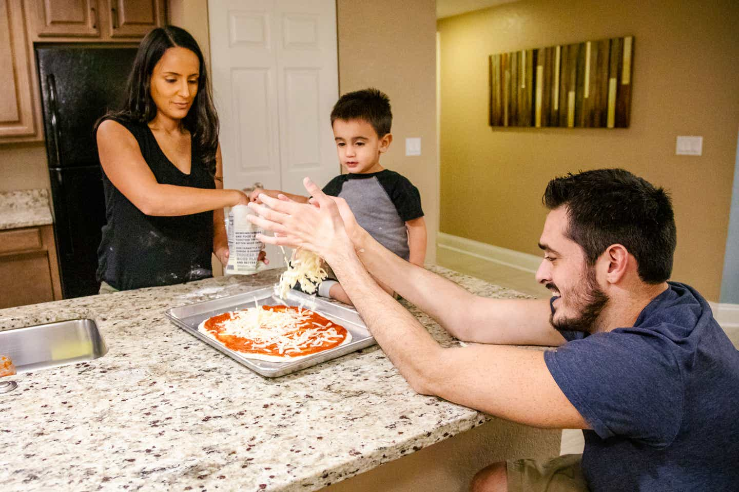 Author, Danny Pitaluga (right), his wife, Val (left) and son, Joey (middle), make a pizza together on the ADA compliant island in the kitchen of our villa located in Orange Lake Resort located in Orlando, Florida.