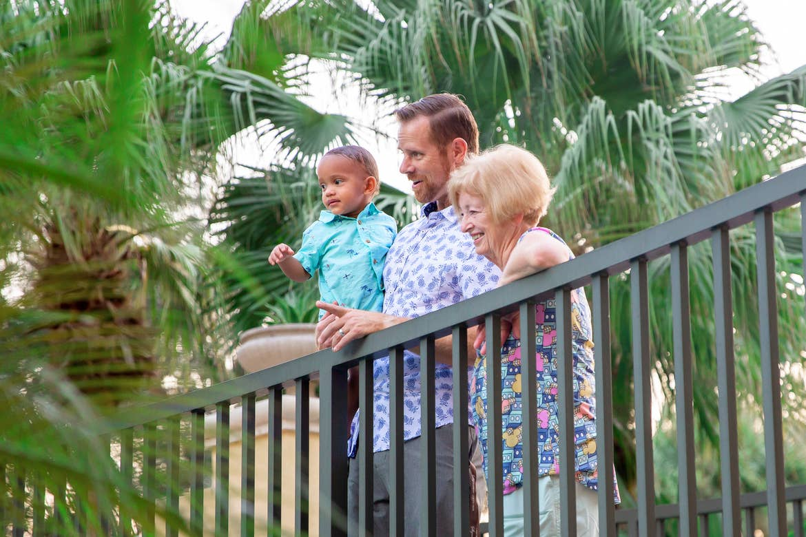 Featured Contributor, Sally Butan's husband stands holding his son next to his mother as they look at the lazy river at Orange Lake Resort near Orlando, Florida.