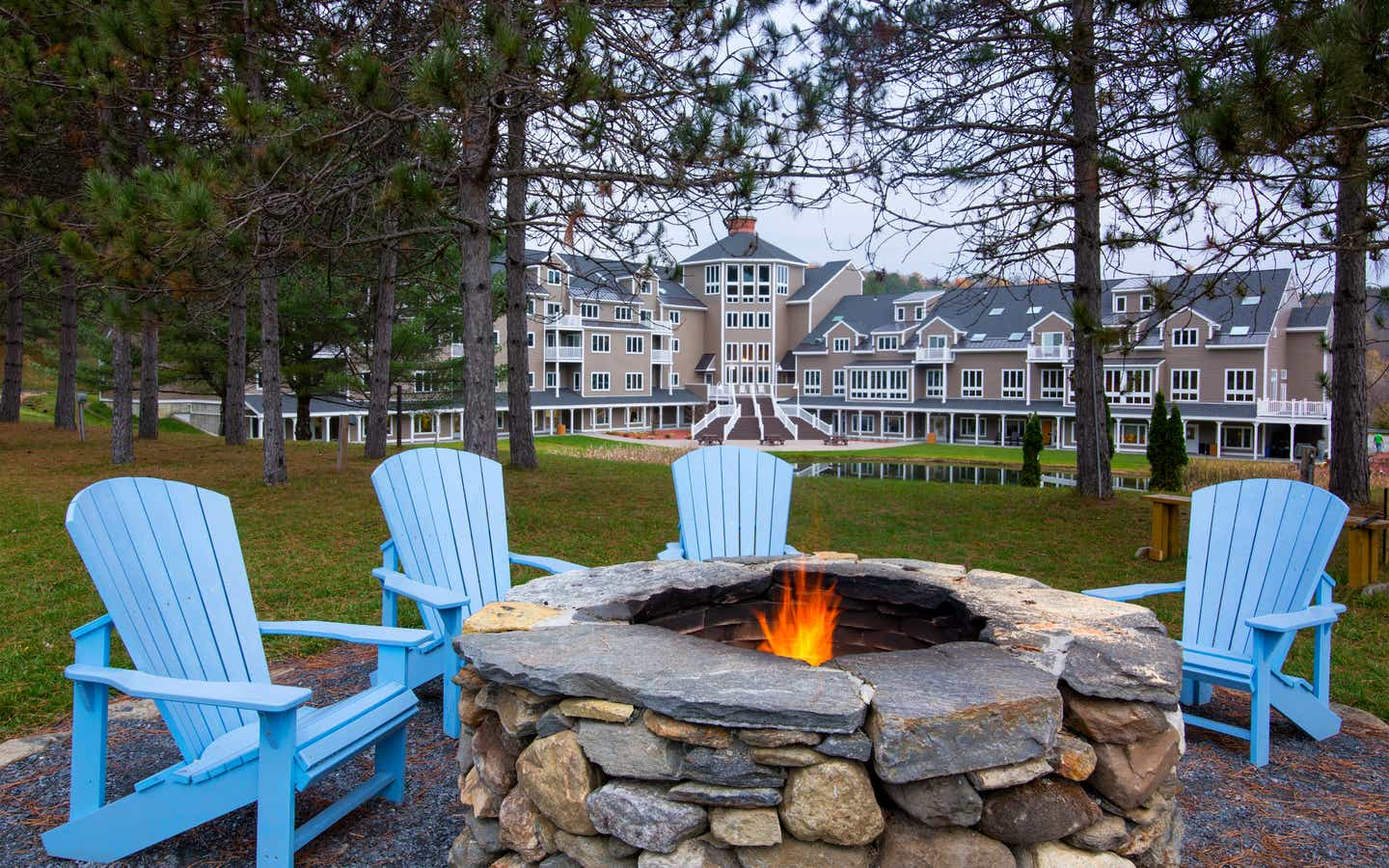 Outdoor fire pit with four blue chairs around it at Mount Ascutney Resort in Brownsville, Vermont.