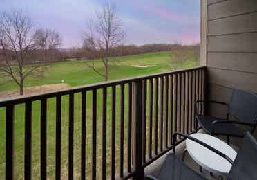 Furnished balcony overlooking vast grassy area in a one-bedroom villa at Lake Geneva Resort