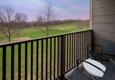 Furnished balcony overlooking vast grassy area in a villa at Lake Geneva Resort