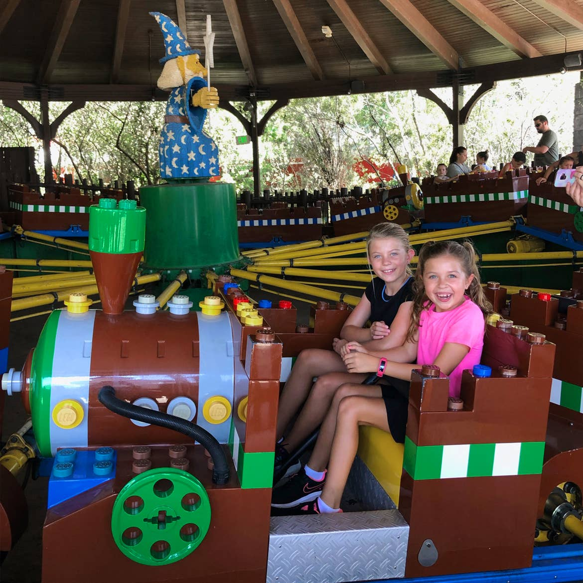 Two young girls sit on a ride vehicle made of LEGOS.