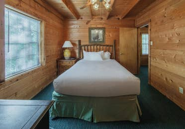 Bedroom in a one-bedroom log cabin at Holly Lake Resort in Holly Lake Ranch, Texas.