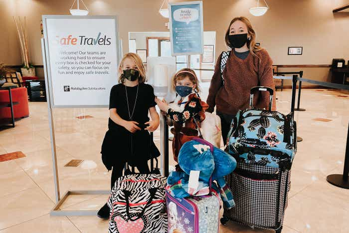 The Haby family poses with suitcases and masks near a 'Safe Travels' sign located in the lobby at our Desert Club Resort located in Las Vegas, Nevada.