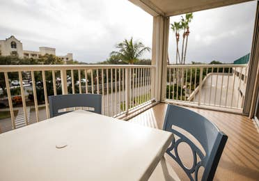 Balcony with outdoor table and chairs in a two-bedroom villa at Cape Canaveral Beach Resort.